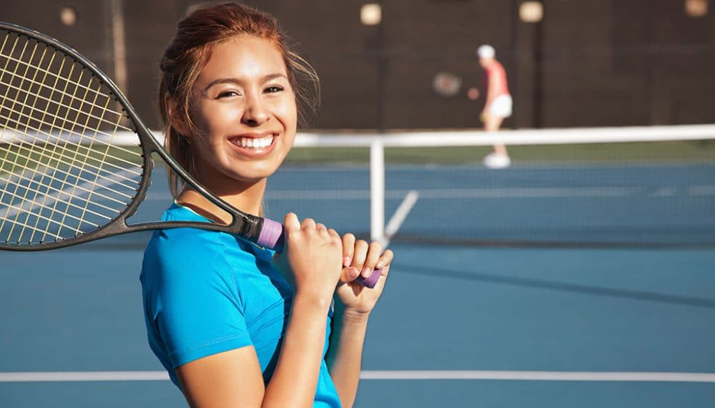 a woman enjoying tennis lessons in her area. Racquet of her shoulder smiling at the camera